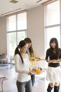 three teens carrying food in a cafeteria at school