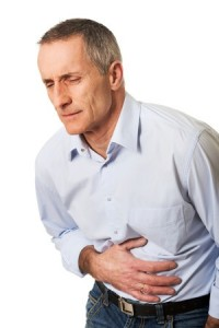 man holding stomach-has pain from eating gluten